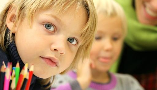 Ett barn i förgrund, ett barn och en vuxen i bakgrund